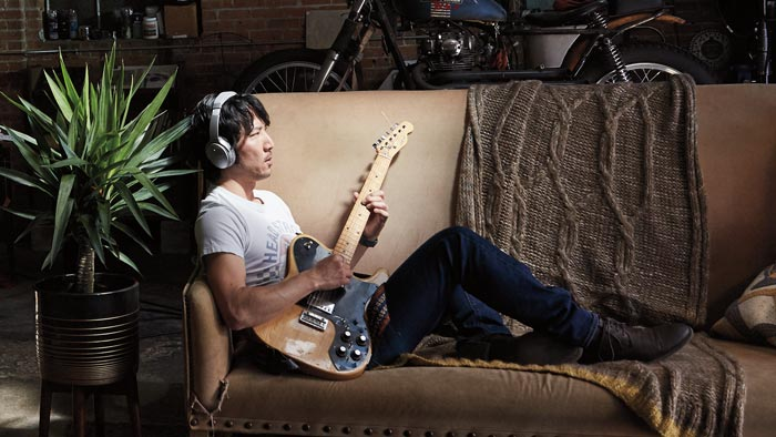 Image of QC35 on the man playing guitar on couch.