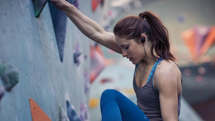 Image of SoundSport wireless worn by woman on climbing wall.