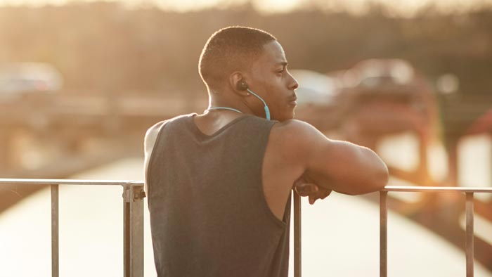 Image of SoundSport wireless worn by man resting on bridge.