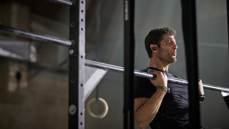 Image of a man sitting on stairs. Bose SoundSport Free wireless headphones.