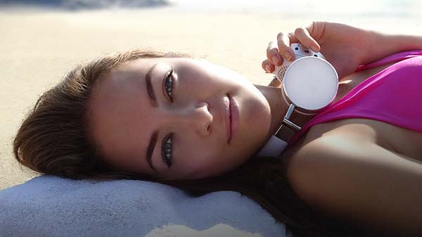Girl wearing Cleer BT headphones sunning on beach